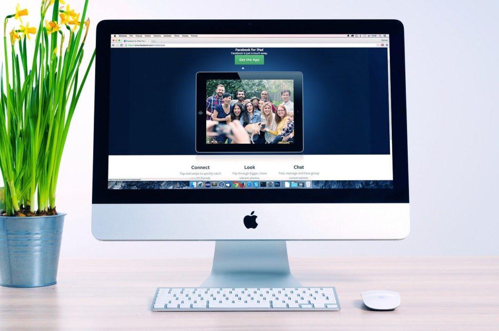 אתר אינטרנט חדשני על מסך מחשב של מאק עם עכבר ומקלדת אלחוטיים לצד עציץ ירוק עם פרחים צהובים
